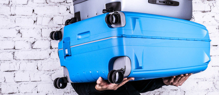 man-holding-three-heavy-suitcases-in-hand-shutterstock_349840742-2-1200×335