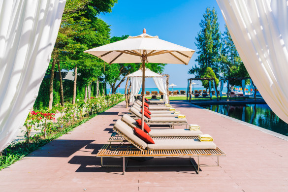 umbrella-pool-and-chair-in-beautiful-luxury-hotel-pool-resort-filter-processing-style-pictures-shutterstock_378577537-2-585x390