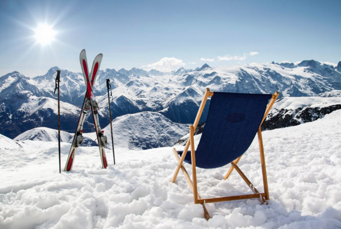 Cross ski and Empty sun-lounger at mountains in winter