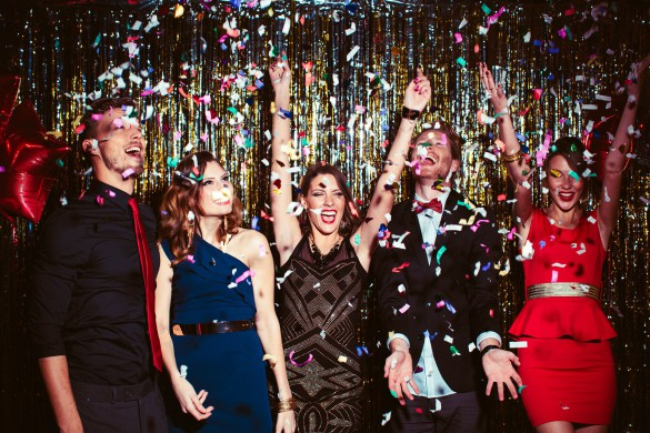 Young people wearing elegant clothes celebrating or having party in front of fringe curtain. They are dancing, smiling and having fun, confetti is in the air, dancing in night club.