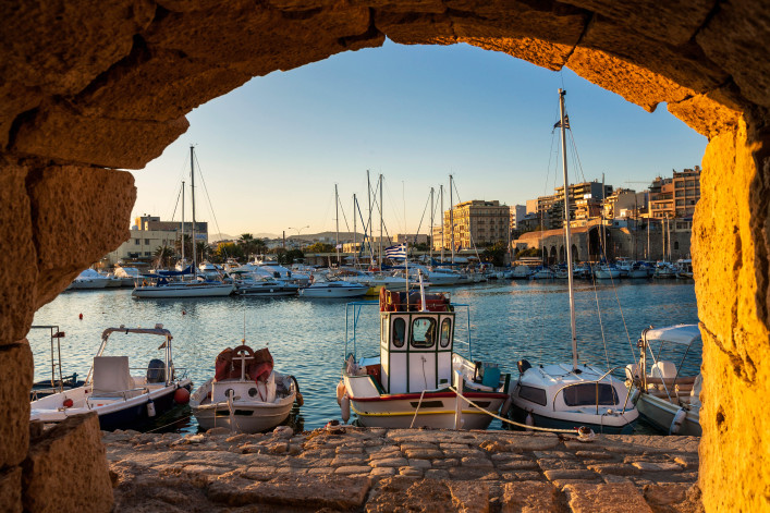 """Fishing boats and sailboat line the dockside in the beautifully set Greek nautic village.Old fortress in Heraklion, Crete - Greece, Venetian Fortress."""