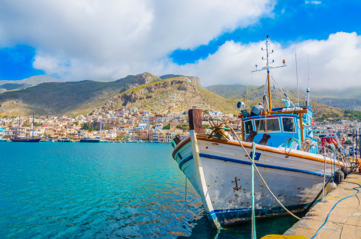 Typical Greek Fishermans' boat standing in harbour with port building in backgound on Greek Island, Greece