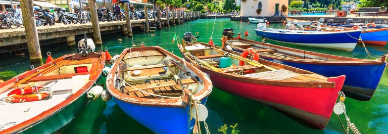 Summer landscape and wooden boats ,Lake Garda, Torbole town, Italy shutterstock_243404224
