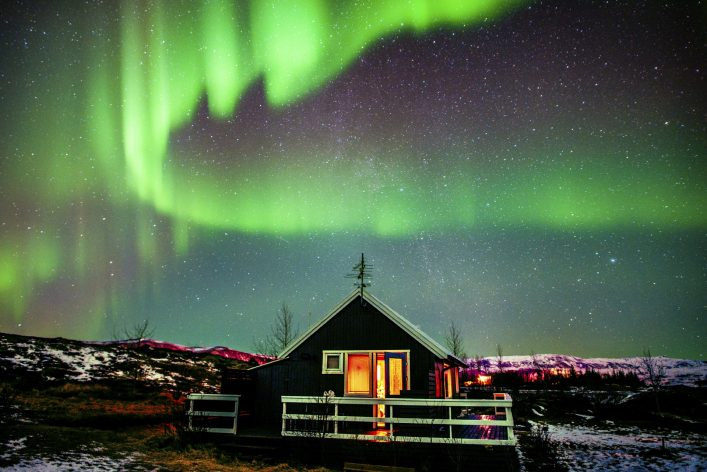 northern-lights-visible-above-small-cabin-in-iceland-istock_000066132119_large-1