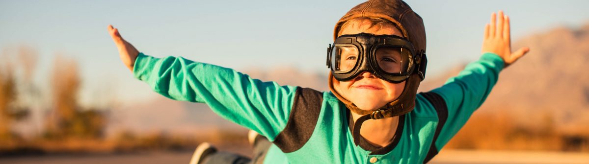 Young Boy with Goggles Imagines Flying on Suitcase