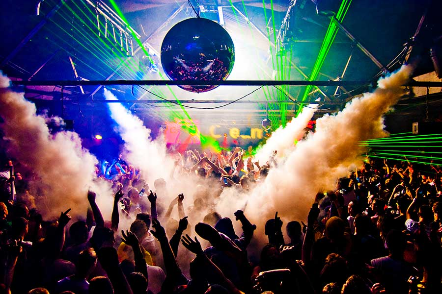 Hands-In-Air-Rave-With-Smoke-Machine-and-Laser-Crowd-Nightclub-shutterstock_94782199-
