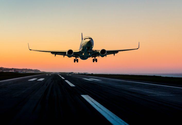 Passenger airplane landing at sunset