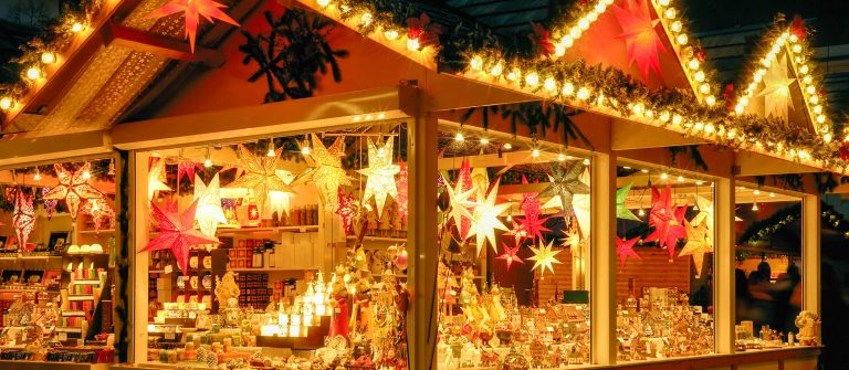 Illuminated Christmas fair kiosk with loads of shining decoration merchandise shutterstock_157503014-2