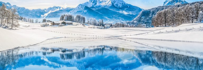Winter wonderland in the Alps reflecting in crystal-clear mountain lake