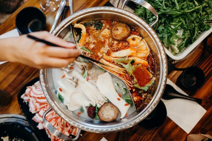 Korean hot pot meal. Hands taking food with chopsticks.
