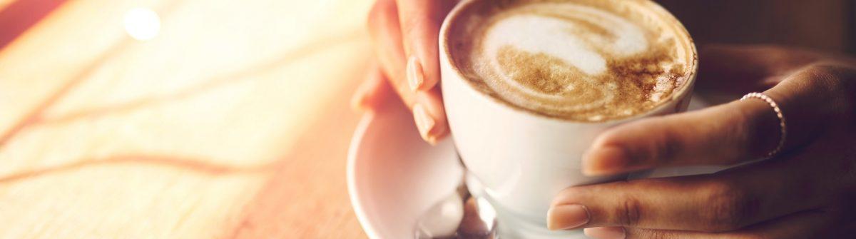 Frau mit einem frischen Kaffee im Café.