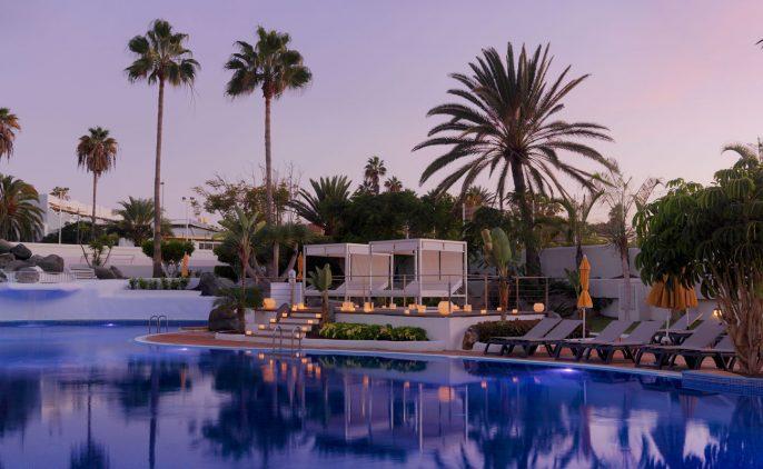 Vista nocturna de las camas balinesas junto a la piscina