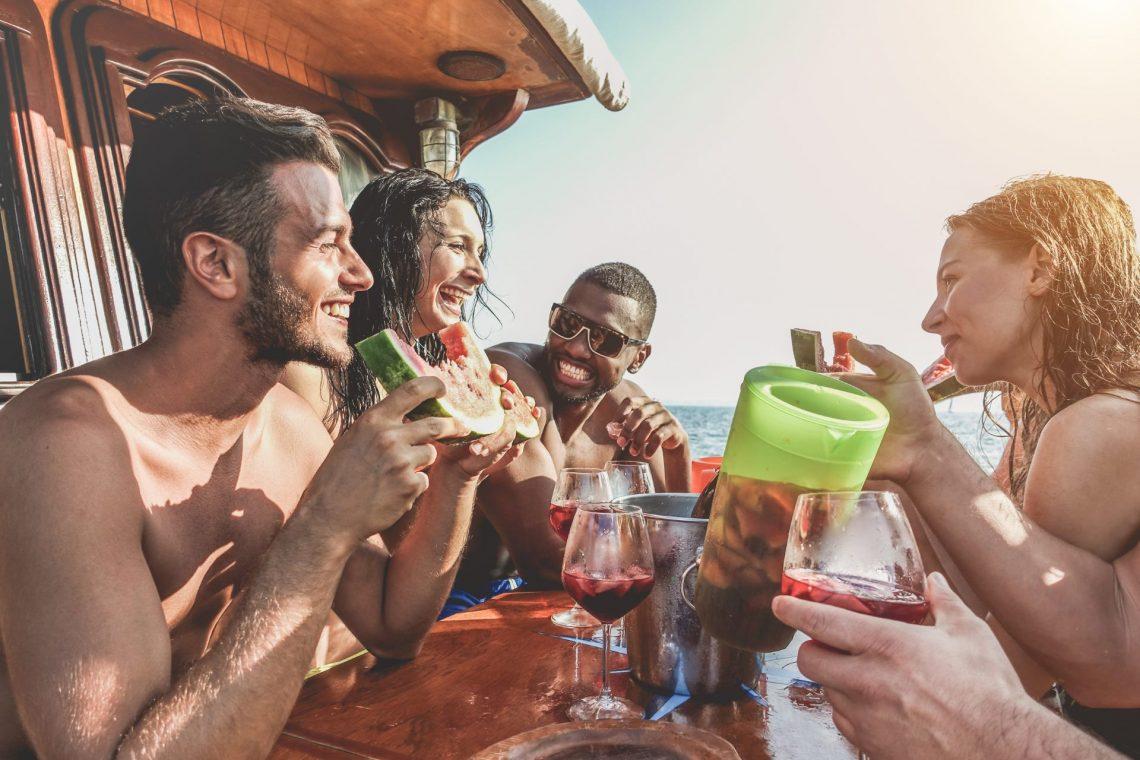 Junge Leute trinken Sangria auf einem Boot