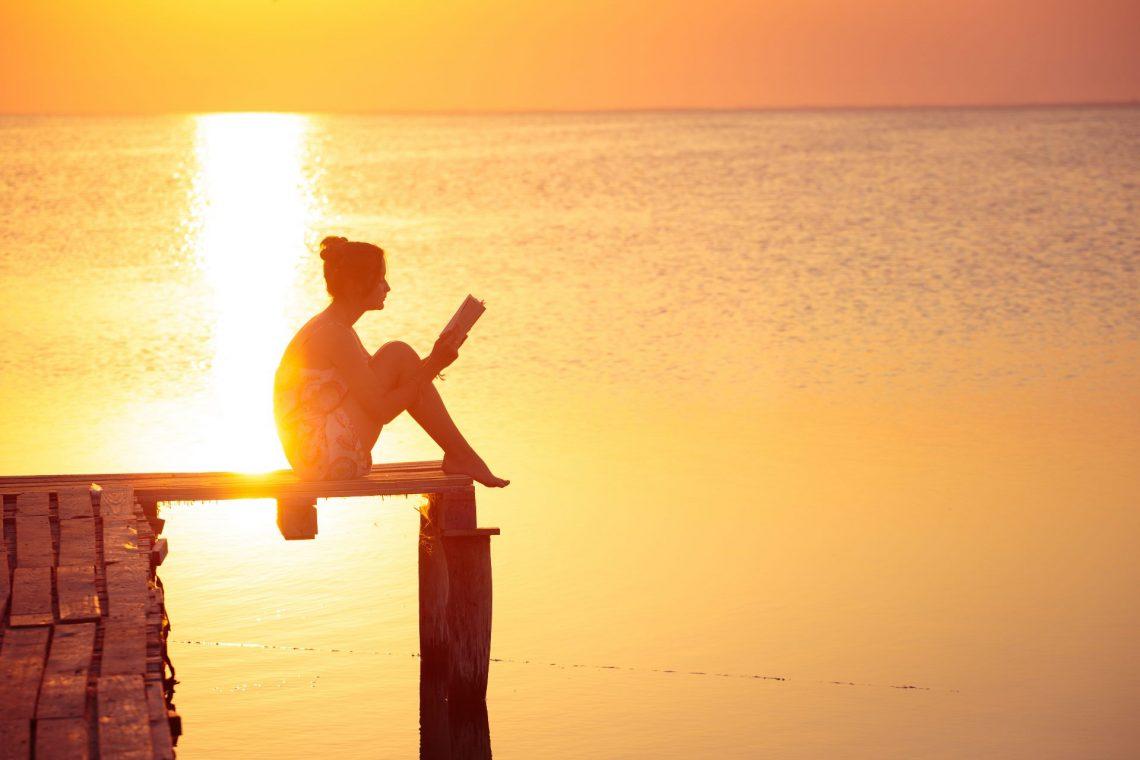 Frau liest bei Sonnenuntergang ein Buch auf einem Steg