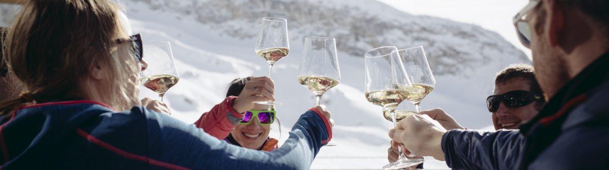 Menschen stoßen mit einem Glas Wein an