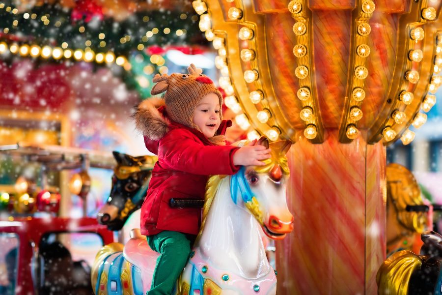 Happy-little-girl-in-warm-red-jacket-and-knitted-reindeer-hat-riding-carousel-horse-during-family-trip-to-traditional-German-Christmas-market.-shutterstock_491208898_min