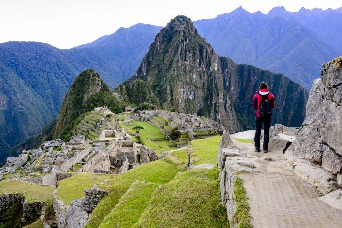 Woman overlooking the Inca ruins of Machu Picchu