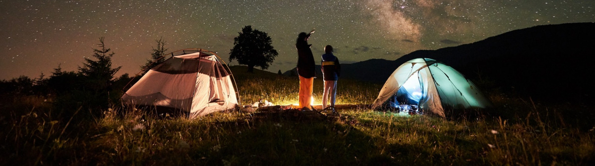 Mother and son tourists resting at camping in mountains at night sky full of stars and Milky way