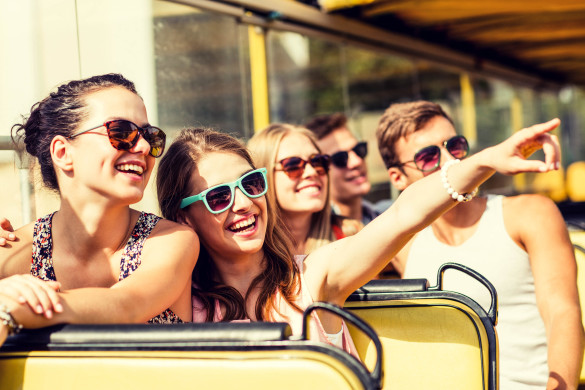 group-of-smiling-friends-traveling-by-tour-bus-shutterstock_281448020-2-585x390