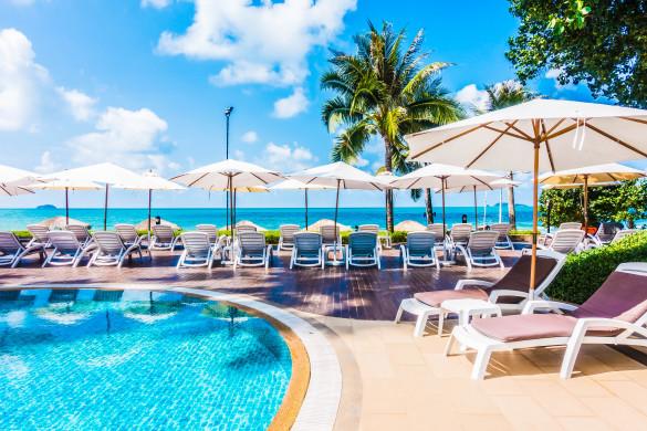 beautiful-luxury-umbrella-and-chair-around-outdoor-swimming-pool-in-hotel-resort-shutterstock_420110824-2-585x390